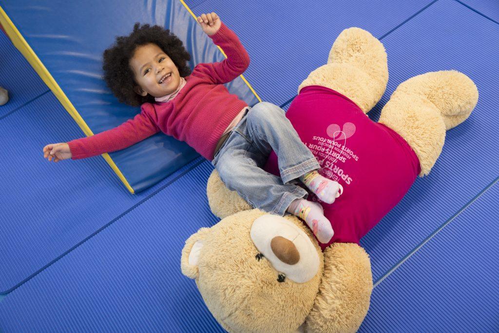 Photo d'une enfant avec sa peluche jouant sur des tapis de sports de Sports Pour Tous