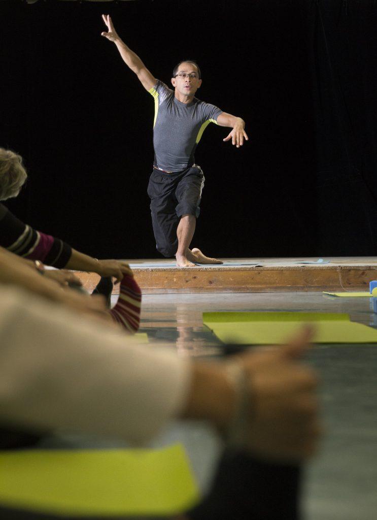 Un instructeur de yoga donnant un cours sur une petite estrade